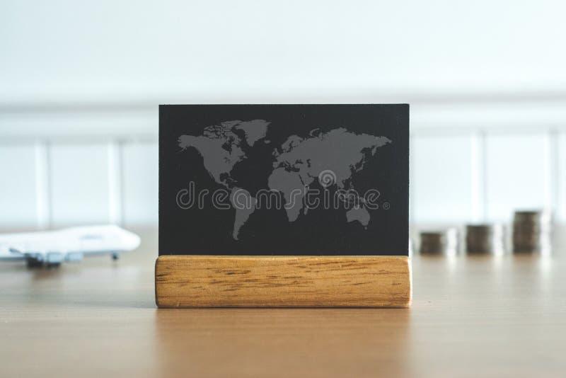 Stäng sig upp på en världskarta på en svart tavla med mynt pengar och flygplan i bakgrund Begrepp för loppbudget royaltyfri foto