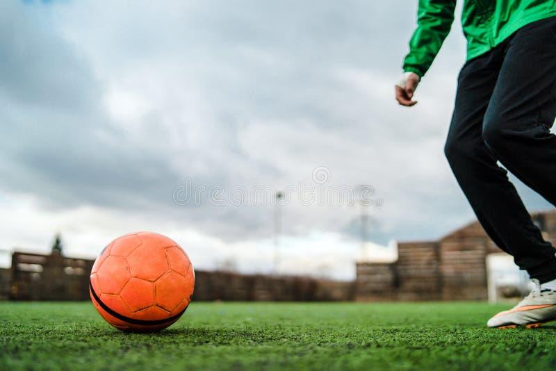 Stäng sig upp på fötter att sparka fotbollbollen arkivfoto
