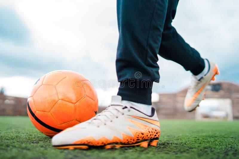 Stäng sig upp på fötter att sparka fotbollbollen royaltyfria foton