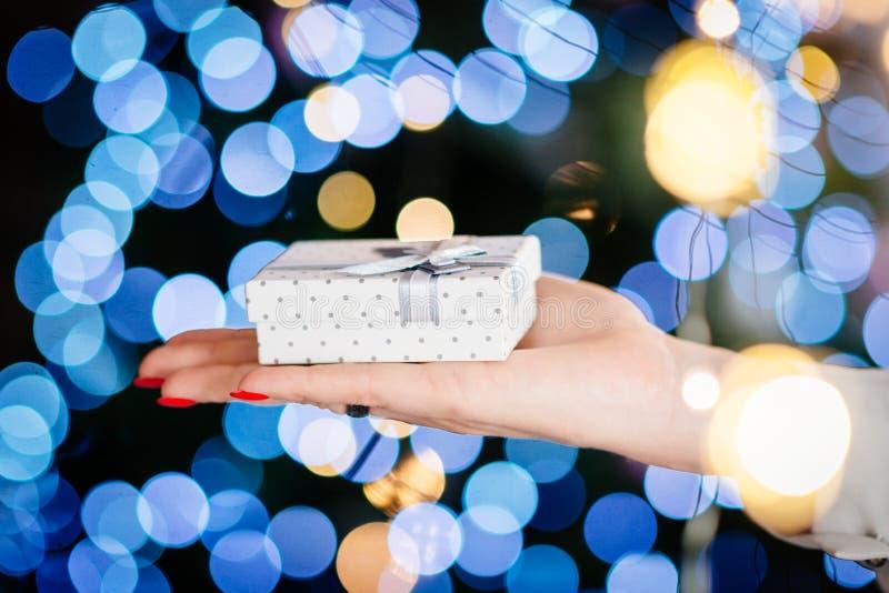 Stäng sig upp på handen för den unga kvinnan som ger julklapp royaltyfri bild