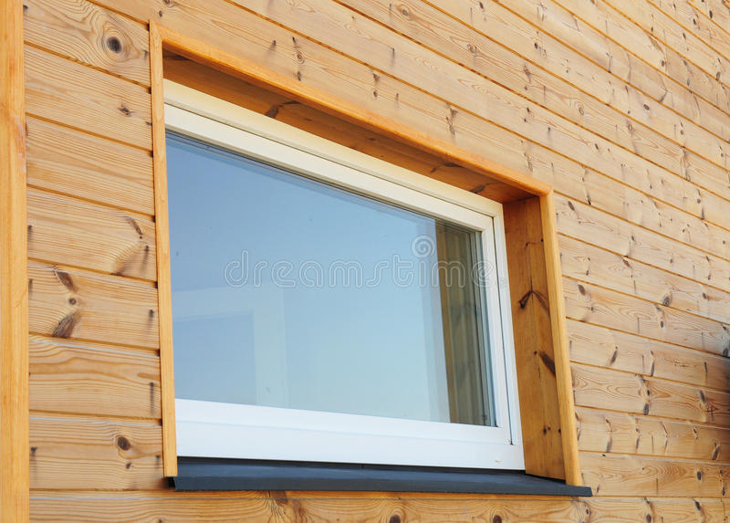 Stäng sig upp på plast- PVC-fönster i ny modern passiv trähusfasadvägg fotografering för bildbyråer