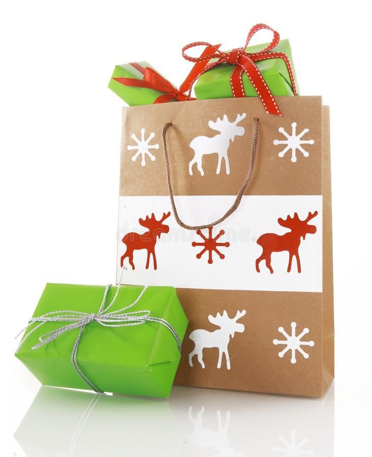 Stäng sig upp pappers- påse för jul med gröna gåvaaskar arkivfoton