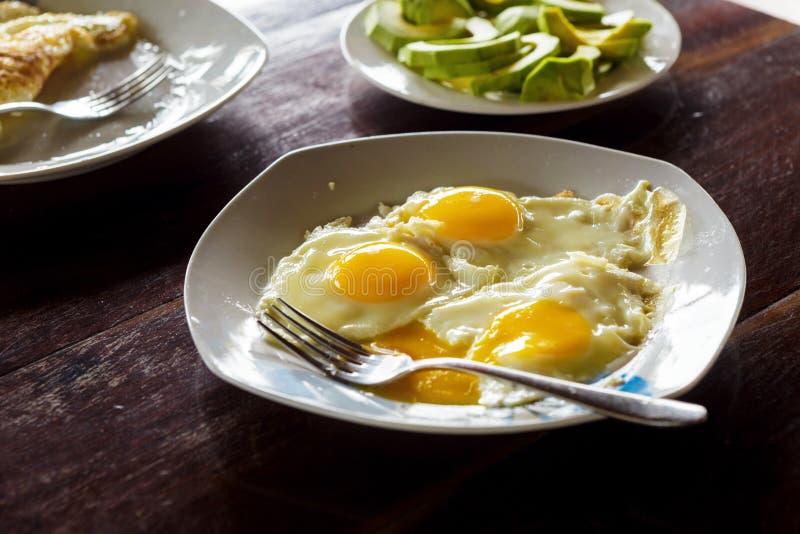 Stäng sig upp plattan stekte ägg med avokadot på trätabellen royaltyfria foton