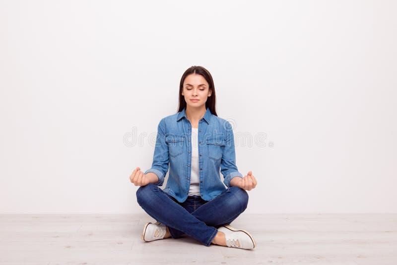 Stäng sig upp portraitt av den lugna tysta tranquile meditativa damen med sammanträde för teckensymbolom i lotusblommaposition på fotografering för bildbyråer