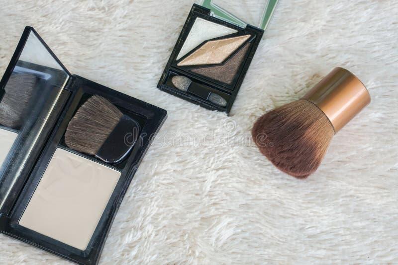 Stäng sig upp pressande pulver och syna shadoepallete med skönhetborsten på pälsbakgrund royaltyfria bilder