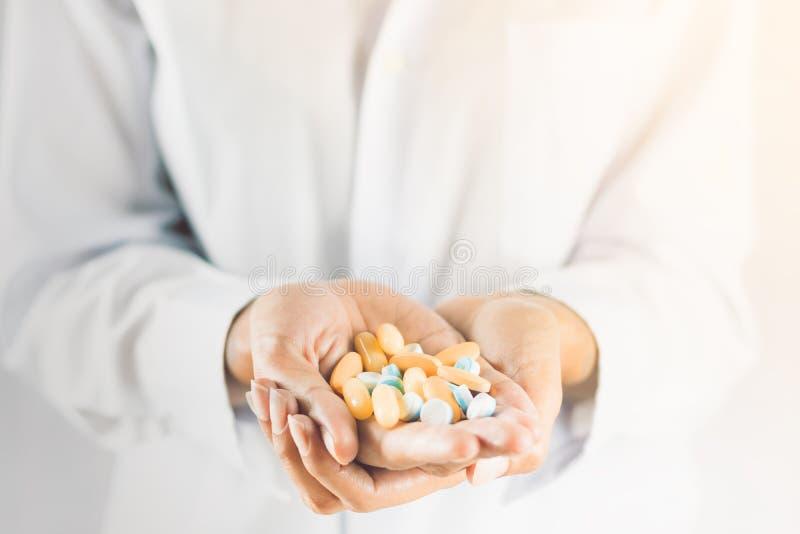 Stäng sig upp preventivpiller på händer, ska ta den manny preventivpilleren royaltyfri bild