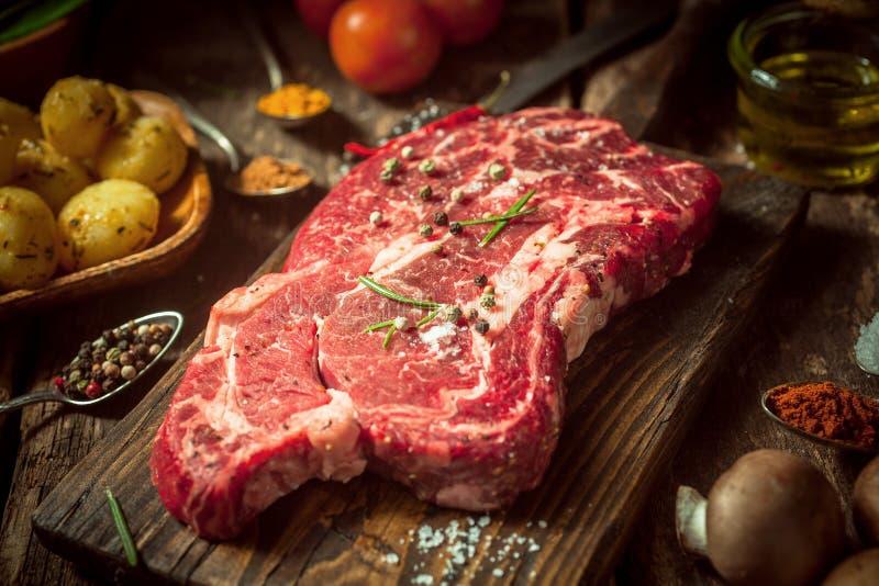 Stäng sig upp rått nötkött- eller grisköttkött på den lantliga tabellen royaltyfri fotografi