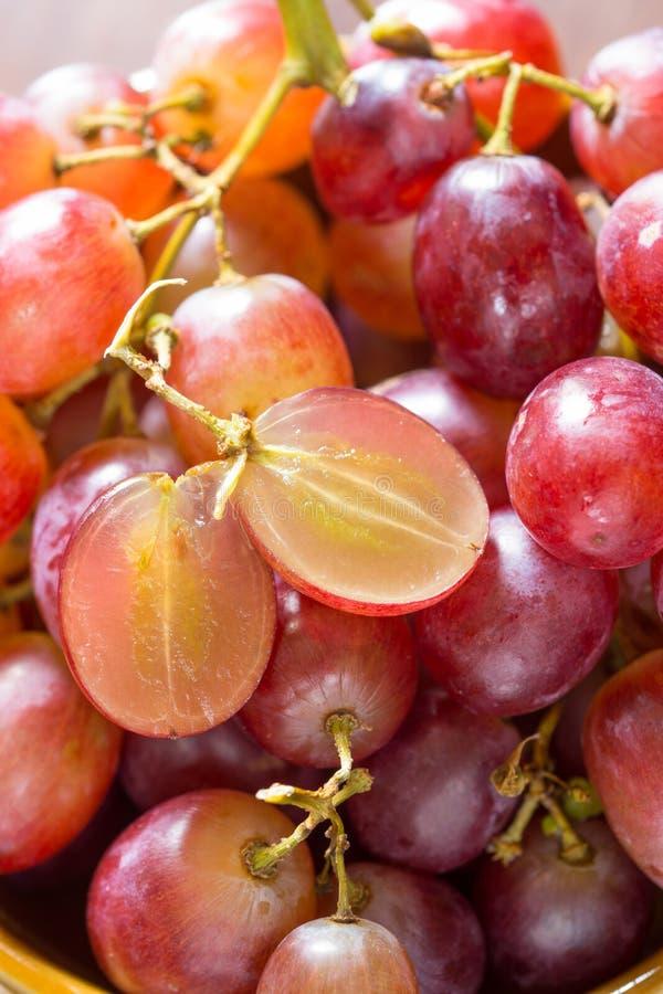 Stäng sig upp röda kärnfria druvor i en keramisk bunke arkivfoto