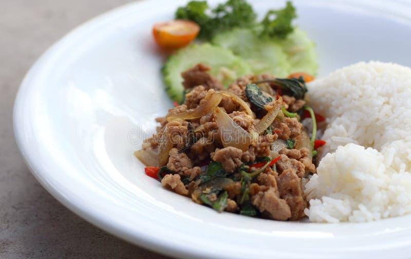 Stäng sig upp ris som överträffas med uppståndelse stekt finhackad griskött och basilika royaltyfri foto