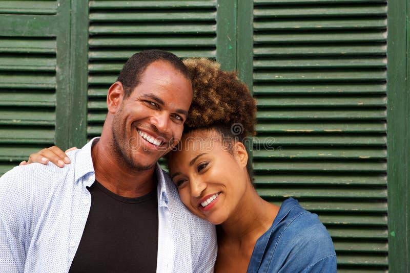 Stäng sig upp romantiska attraktiva par, i att skratta för omfamning royaltyfria bilder