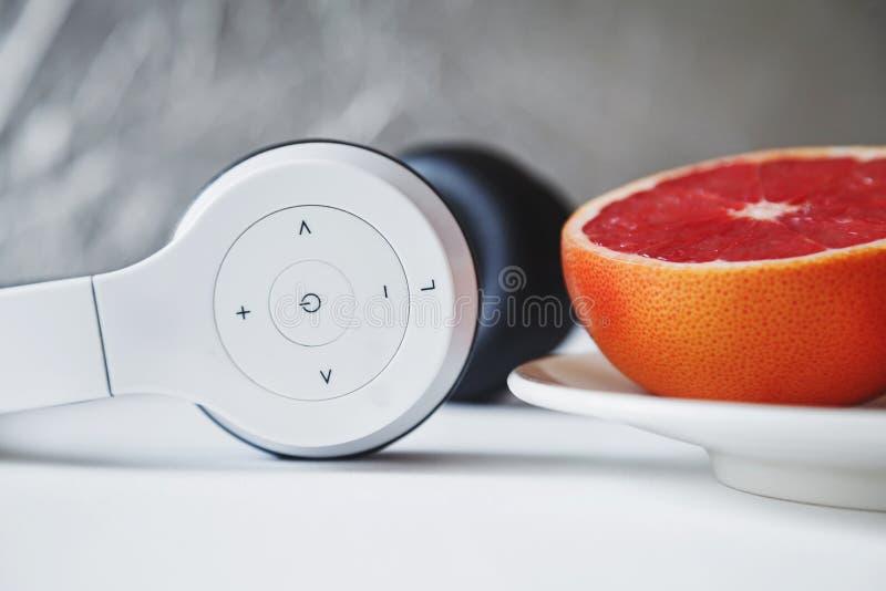 Stäng sig upp sammansättning av den vita minimalist hörlurar med mikrofon och halva av fre royaltyfria foton