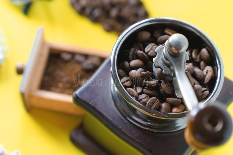 Stäng sig upp selektiva kaffebönor för den bästa sikten och jordkaffebönan i tappningträkaffekvarn på gul bakgrund royaltyfri foto