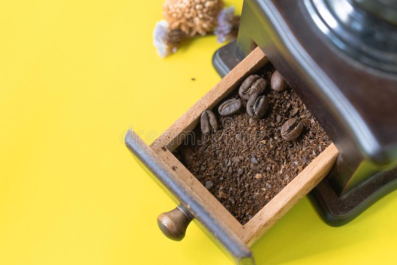 Stäng sig upp selektiva kaffebönor och den grundade kaffebönan i tappningträkaffekvarn på gul bakgrund royaltyfri bild
