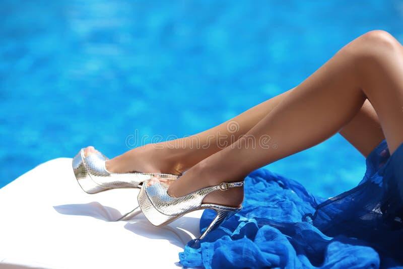 Stäng sig upp sexiga brunbrända långa ben i höga häl som ligger på solstol arkivfoton