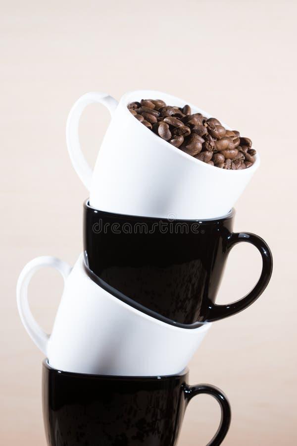Stäng sig upp sikt av att stå svartvita koppar på bunten royaltyfria foton