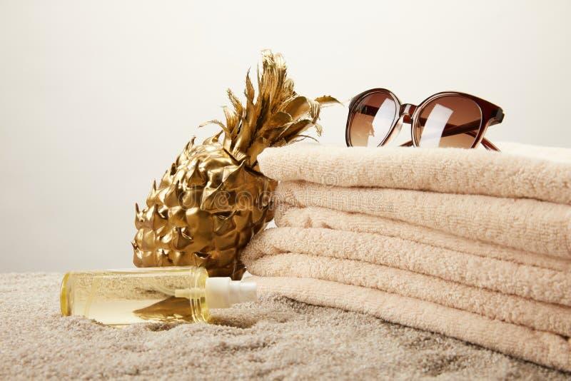 stäng sig upp sikt av bunten av handdukar, solglasögon och att garva olje- och guld- dekorativ ananas på sand på den gråa bakgrun royaltyfri foto