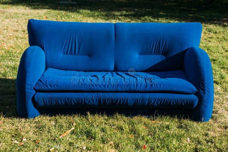 stäng sig upp sikt av det blåa soffaanseendet på grön gräsmatta arkivfoton