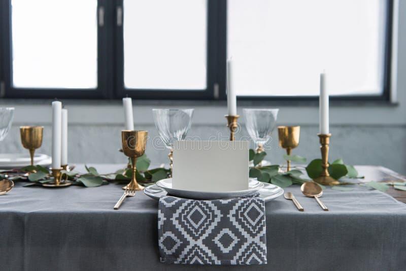 stäng sig upp sikt av det tomma kortet på plattor på tabletopen med den härliga lantliga inställningen för gäster royaltyfri fotografi