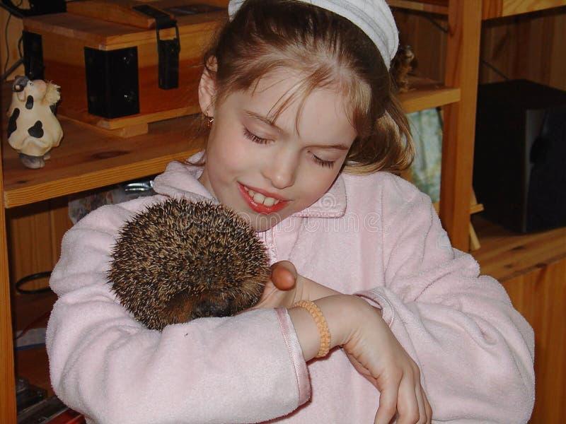 Stäng sig upp sikt av en ung flicka som rymmer en gulligt igelkott och le royaltyfri bild