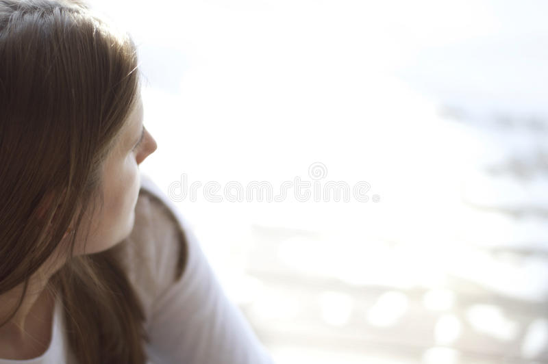 Stäng sig upp sikt av en ung kvinna som ut ser på vattnet arkivbilder