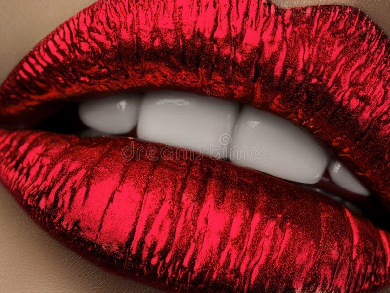 Stäng sig upp sikt av härliga kvinnakanter med röd metallisk läppstift fotografering för bildbyråer