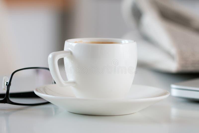 Stäng sig upp sikt av koppen för vitt kaffe på tabellen med exponeringsglas och nyheterna royaltyfria foton