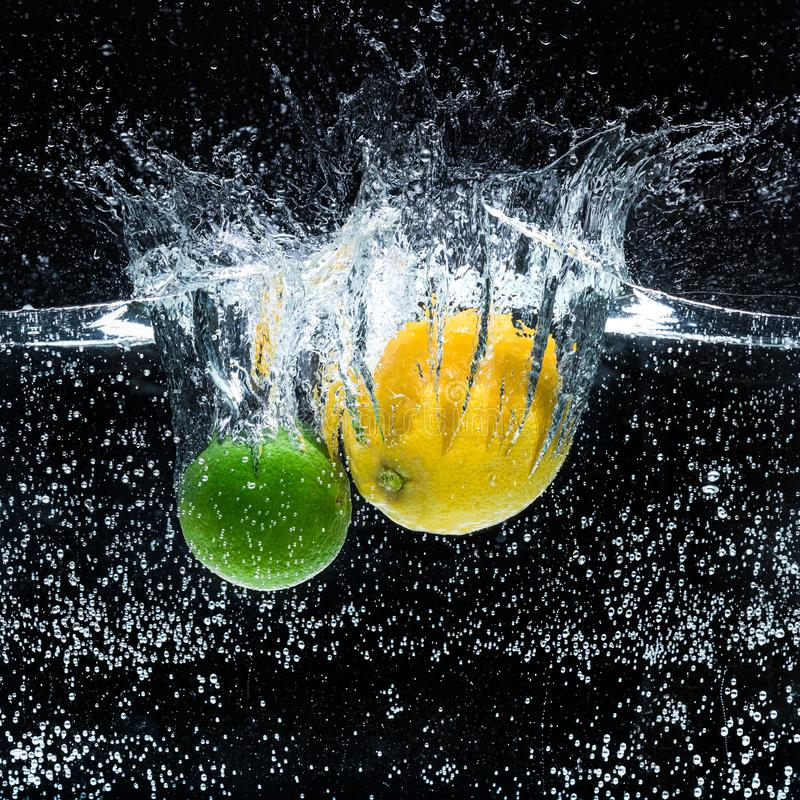 stäng sig upp sikt av nya citroner och limefrukter i vatten royaltyfri foto