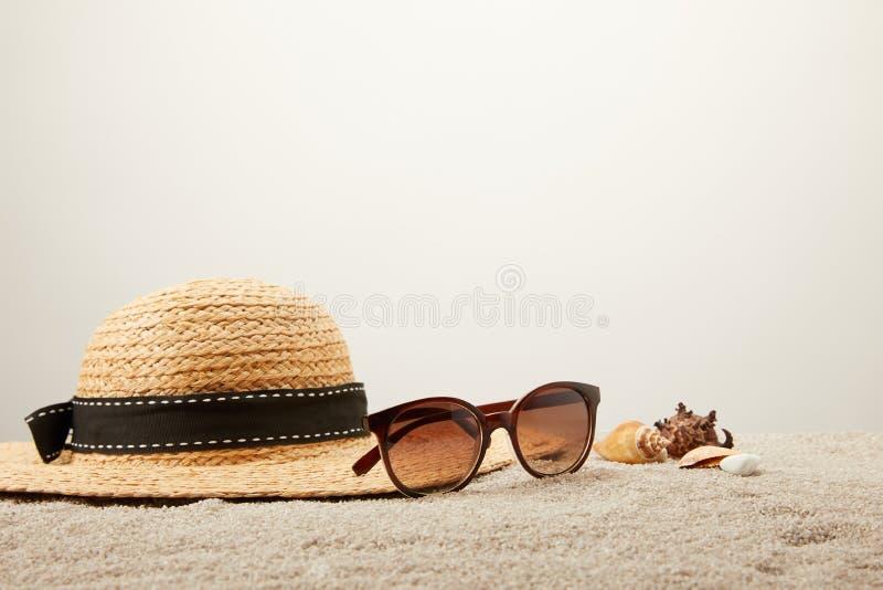 stäng sig upp sikt av sugrörhatten, solglasögon och snäckskal på sand på den gråa bakgrunden arkivfoto