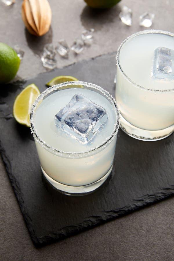 stäng sig upp sikt av träpressen, uppfriskande sura alkoholcoctailar med limefrukt och is på den gråa tabletopen royaltyfri bild
