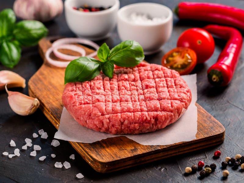 Stäng sig upp sikt av två biffkotletter för rått kött för hamburgare med grönsaker arkivfoton
