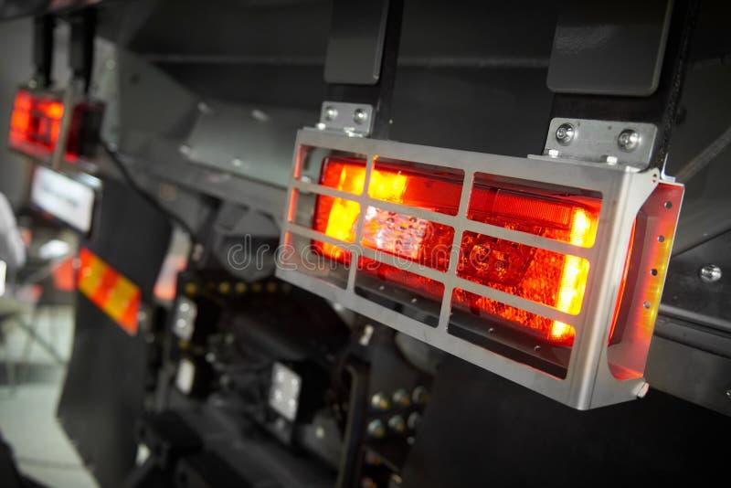 Stäng sig upp sikt på bakre rött och gult ljus för bilperson som ger drickslastbil med hus för metall för räkningen för skölden f royaltyfri fotografi