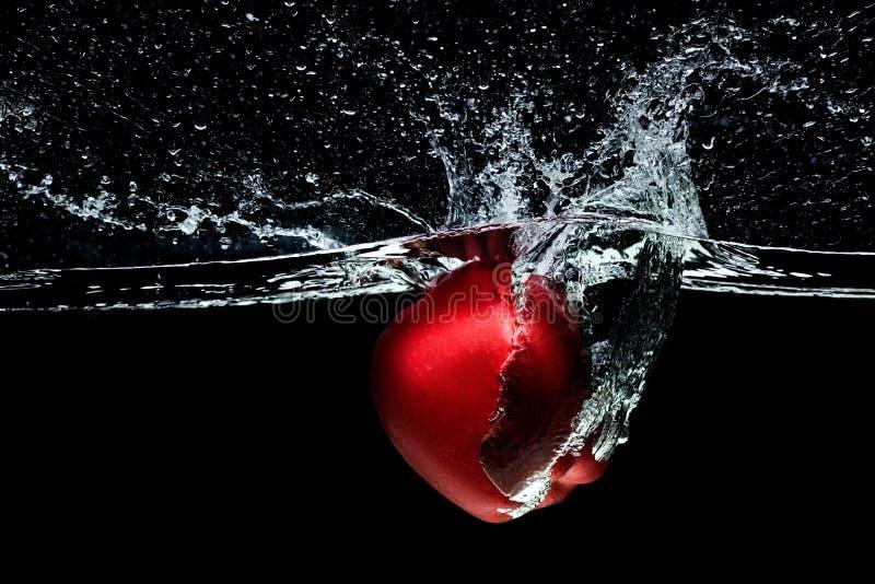 stäng sig upp sikten av det röda äpplet som faller in i vatten fotografering för bildbyråer