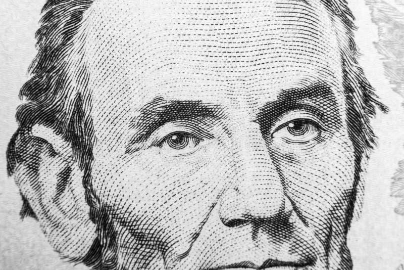 Stäng sig upp siktsståenden av Abraham Lincoln på den en räkningen för dollar fem Bakgrund av pengarna räkning för dollar 5 med A royaltyfria bilder