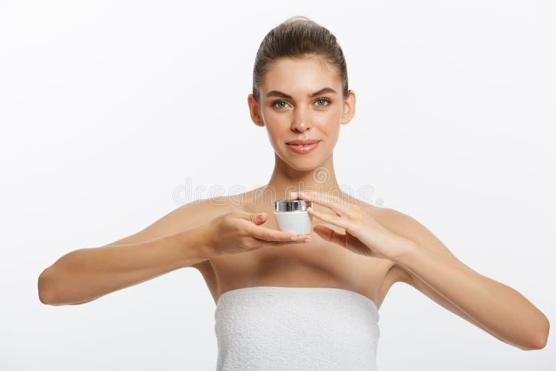 Stäng sig upp skönhetståenden av en le härlig halv naken kvinna som applicerar framsidakräm som isoleras över vit bakgrund fotografering för bildbyråer