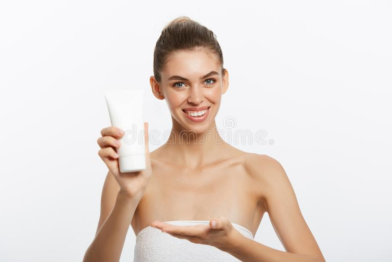 Stäng sig upp skönhetståenden av en le härlig halv naken kvinna som applicerar framsidakräm som isoleras över vit bakgrund royaltyfri bild