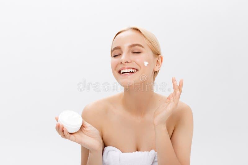 Stäng sig upp skönhetståenden av en skratta härlig halv naken kvinna som applicerar framsidakräm som isoleras över vit bakgrund royaltyfri foto