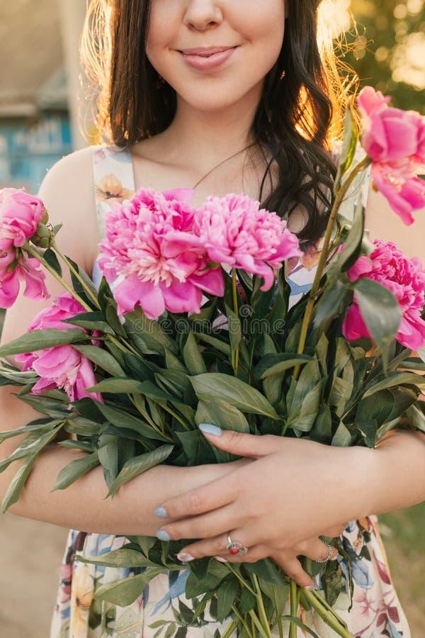 Stäng sig upp skönhetståenden av en ung kvinna med rosa peones Flickan smilling, och solnedgången är bak henne royaltyfria foton