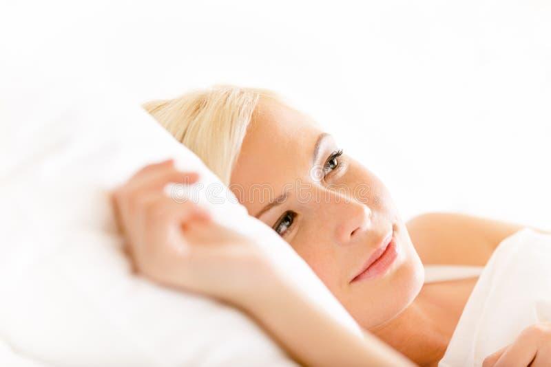 Stäng sig upp skott av att ligga i sängkvinna arkivfoton