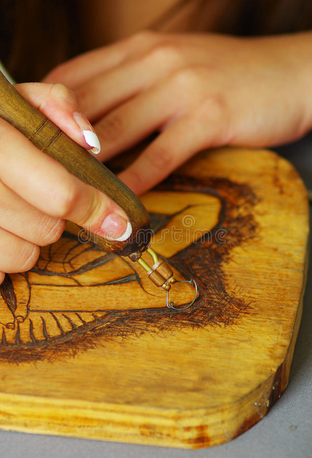 Stäng sig upp skott av den wood bränningen för händer med pyrographypennan arkivbild