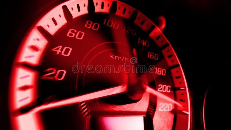 Stäng sig upp skott av en hastighetsmeter i en bil med rött ljushastighet på 220 Km/H i tävlings- bil för begrepp arkivfoto