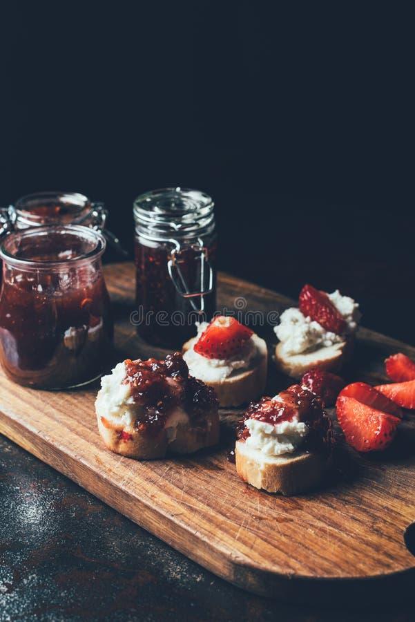 stäng sig upp skott av krus med driftstopp, smörgåsar med gräddost, jordgubbeskivor och fruktdriftstopp på skärbräda royaltyfri foto