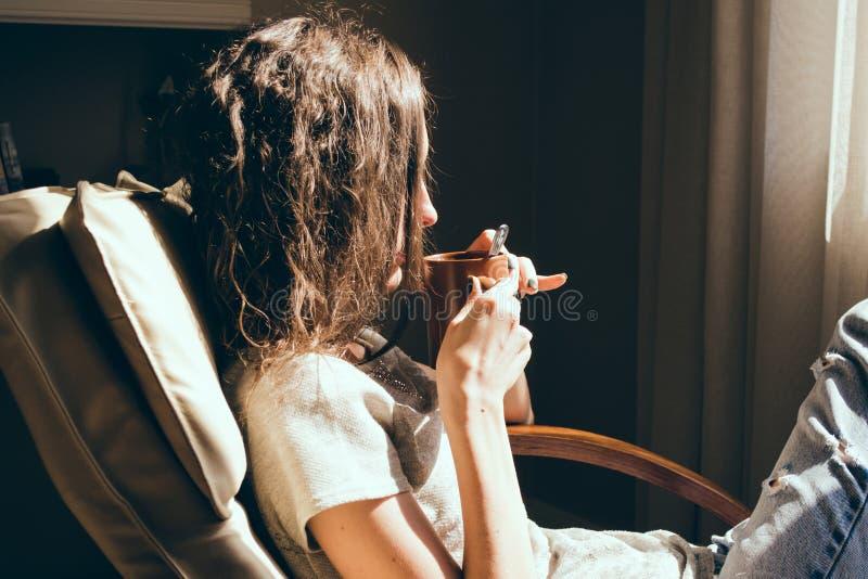 Stäng sig upp ståendekvinnan som kopplar av i bekväm modern stol nära fönster i livingroom som dricker te Varmt naturligt ljus he arkivbilder