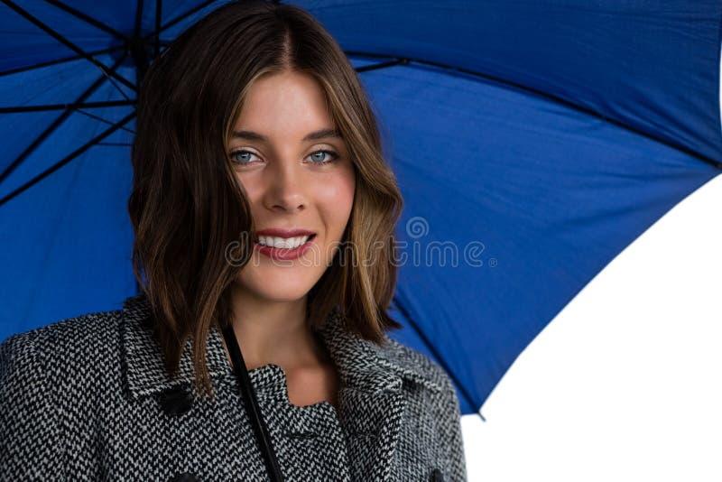 Stäng sig upp ståenden av att le kvinnan med det blåa paraplyet royaltyfri bild