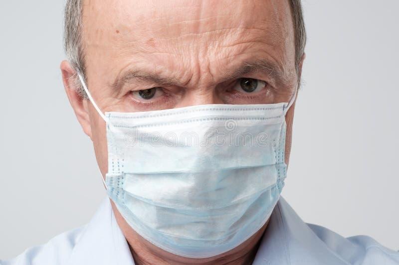 Stäng sig upp ståenden av den allvarliga mannen i special läkaremaskering Han ser allvarlig Mature erfor doktorn fotografering för bildbyråer