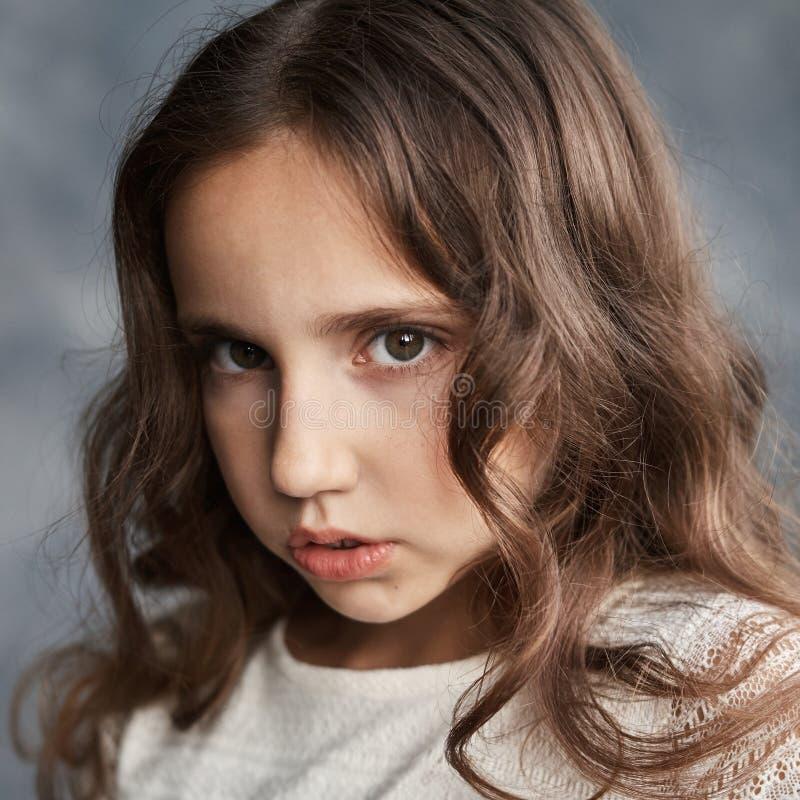 Stäng sig upp ståenden av den allvarliga unga caucasian flickan med lockigt hår och perfekt sund hud royaltyfri bild