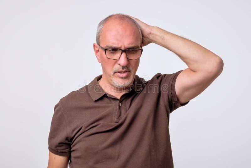Stäng sig upp ståenden av den eftertänksamma mogna mannen i brun t-skjorta royaltyfri foto