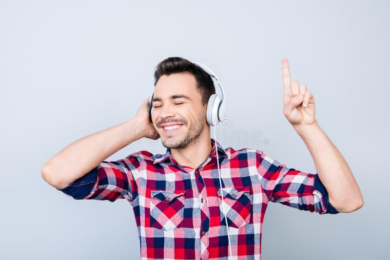 Stäng sig upp ståenden av den gladlynta unga mannen som tycker om att lyssna till högt royaltyfri fotografi