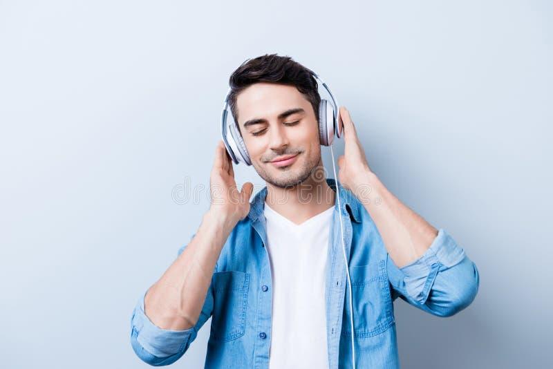 Stäng sig upp ståenden av den gladlynta unga mannen som tycker om att lyssna till högt arkivbilder