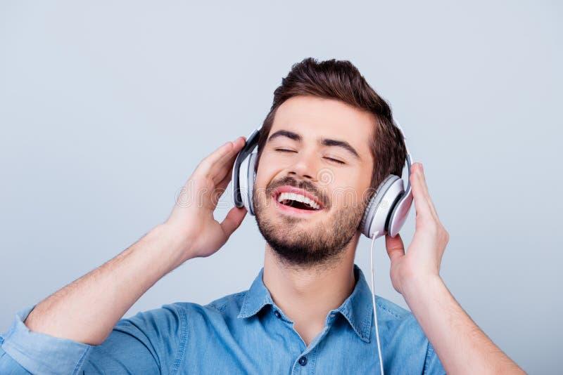 Stäng sig upp ståenden av den gladlynta unga mannen som tycker om att lyssna till högt royaltyfria bilder