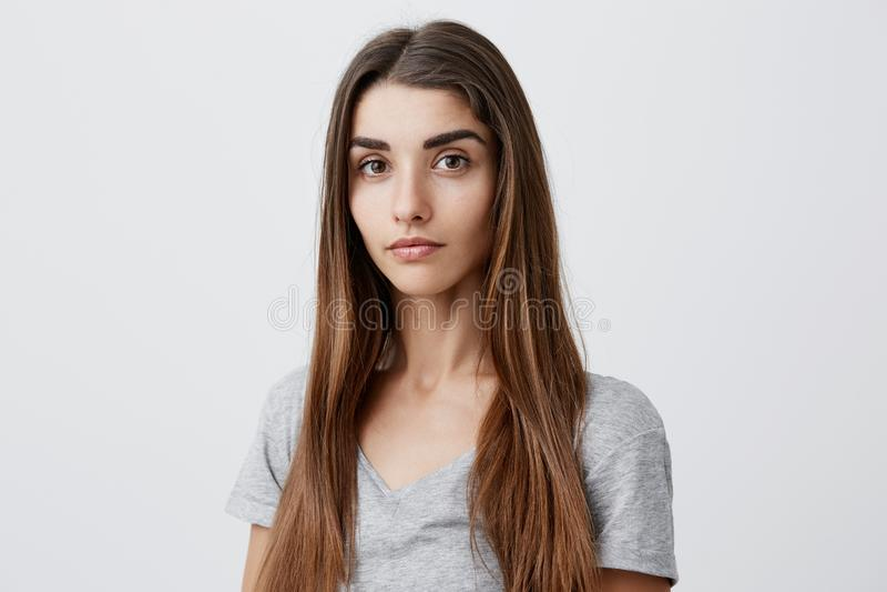 Stäng sig upp ståenden av den härliga allvarliga mörker-haired caucasian kvinnan med den långa frisyren i den tillfälliga gråa sk royaltyfria bilder